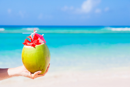 fresh coconut cocktail with umbrella in hand