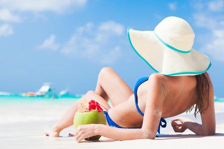woman in bikini with fresh coconut juice on tropical beach photo