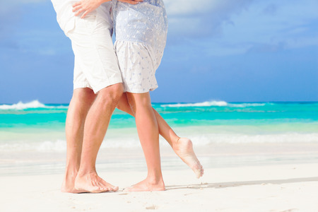 hugging legs: legs of young hugging couple on tropical turquoise beach Stock Photo