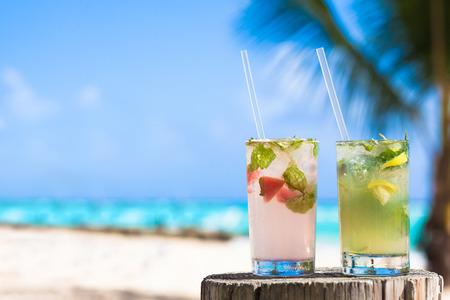 coconut: hai ly cocktail mohito ướp lạnh và kính mát trên bàn gần bãi biển