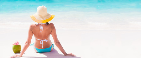 back view of young beautiful  woman with coconut relaxing at sunny tropical beach Standard-Bild