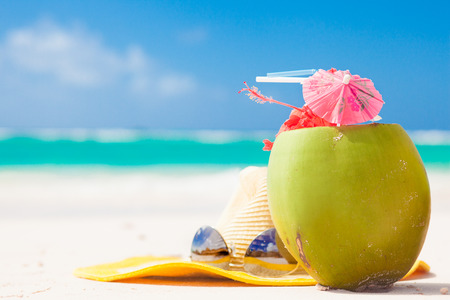 picture of fresh coconut cocktail and blue sunglasses on tropical beach