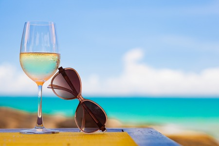 glass of chilled white wine and sunglasses on table near the beach Stock Photo