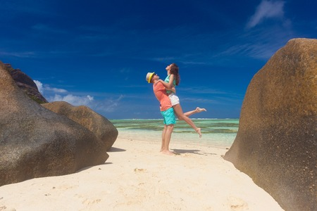 young couple relaxing at beach. Anse Source d`Argent, Seychelles Stock Photo