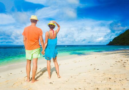 sunhat: Couple wearing bright clothes on a tropical beach. Mahe, Seychelles