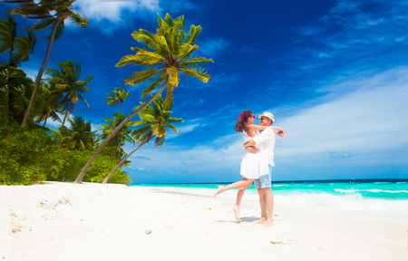 happy young couple in white clothes having fun by the beach
