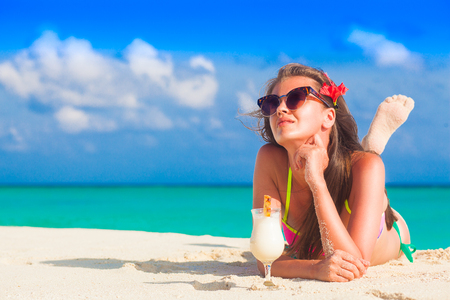 vrouw in bikini ontspannen op wit zandstrand met pina colada cocktail