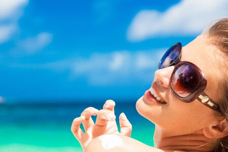suncare: Close up of young woman in sunglasses putting sun cream on shoulder
