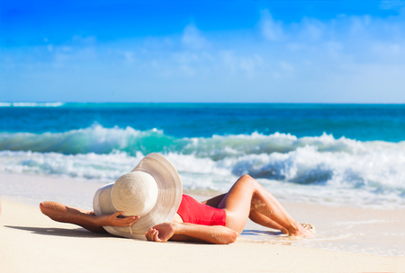 back view of long haired girl in red swimsuit and straw hat on tropical caribbean beach Standard-Bild