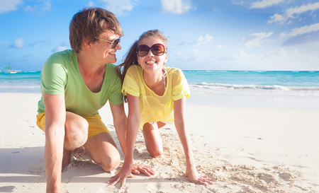 Closeup of happy young caucasian couple in sunglasses smiling on beach Stock Photo