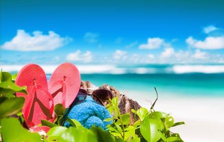pink flip flops, sunglasses and blue towel on a tropical Seychelles beach. Mahe island