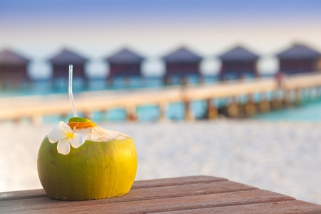 Fresh coconut cocktail on a tropical beach. evening