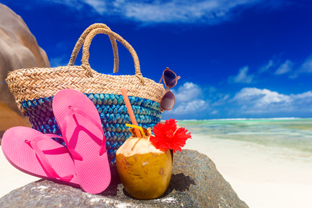 straw bag, pink flip flops, sunglasses and coconut on a tropical Seychelles beach. La Digue island