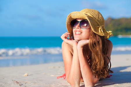 woman in sun hat and swimsuit at beach. Praslin, Seycheles Stock Photo