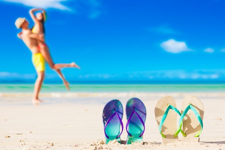 picture of two flip flops with young couple on beach background Stock Photo