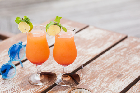 two delicious fruit cocktails decorated with lime on wooden table by the beach