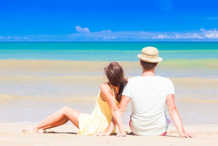 back view of couple sitting on a tropical beach on Maldives 写真素材