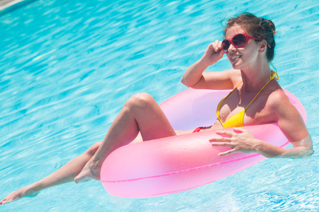 pretty woman floating with pink rubber inflatable ring in swimming pool and having fun Фото со стока