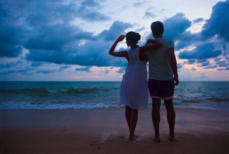 zonsondergang silhouet van een jong koppel in liefde knuffelen op het strand