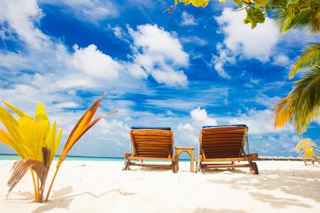 two beach chairs on white sand topical beach. Maldives