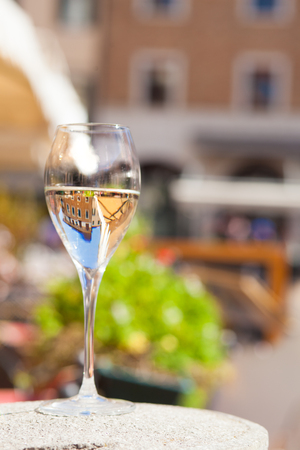 Glass of chilled white wine over sunset city background