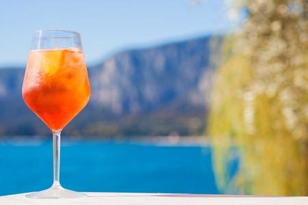 Bicchiere di delizioso cocktail Aperol Spritz su sfondo di montagne sfocate