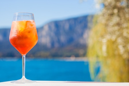 Glass of delicious Aperol Spritz cocktail on blurred mountains background