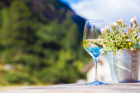 Glass of chilled white wine on a rocky mountain background.