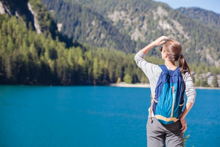 Woman with backpack looking at Braies Lake with mountains on background. Dolomites, South Tyrol, Italy, Europe Stock Photo