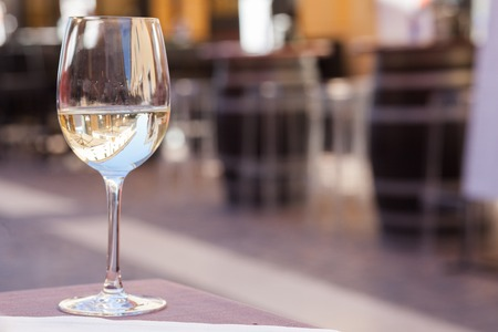 Glass of chilled white wine on Garda streets background