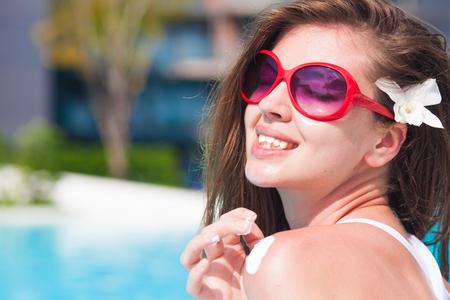 young woman applying sun cream uv protection