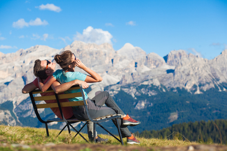Hikers with backpacks sitting on bench on top of a hill and enjoying mountains view. Dolomiti, Alta Badia Archivio Fotografico - 123949683