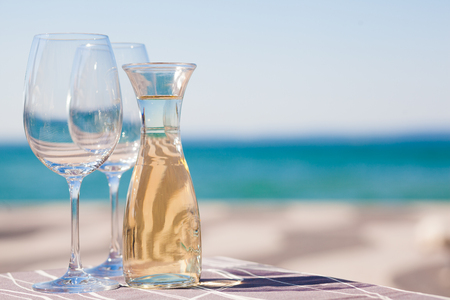 The carafe of white wine and a glass of wine by Garda Lake beach Banque d'images - 123952195