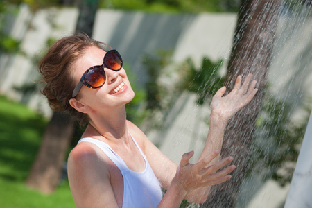 young woman refreshing in tropical shower