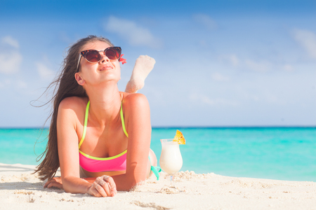 bella donna dai capelli lunghi con un delizioso cocktail di pina colada sulla spiaggia. Maldive