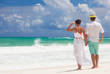Young happy honeymoon couple in white clothes on seashore