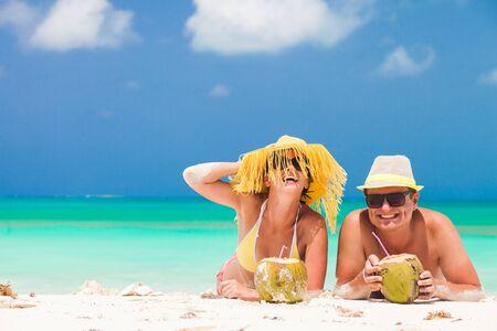 Feliz pareja joven tumbado en una playa tropical en Barbados y bebiendo un cóctel de coco Foto de archivo