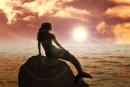 Eine Meerjungfrau während des Sonnenuntergangs auf den Felsen sitzen Standard-Bild