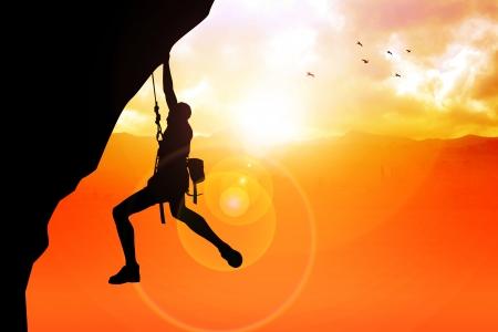 kockázatos: Silhouette illusztráció egy ember alak lóg a szikla Stock fotó