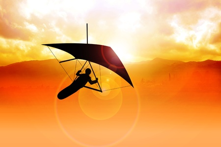 glider: Silhouette of a man figure gliding during sunrise