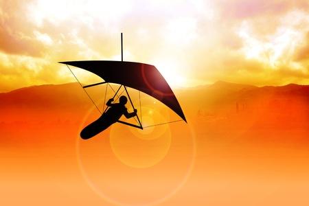 aerodynamics: Silhouette of a man figure gliding during sunrise