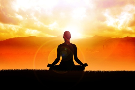 inner peace: Silhouette of a woman figure meditating in the outdoors  Stock Photo