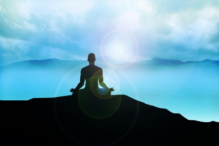 Silhouette of a man figure meditating on the mountain photo