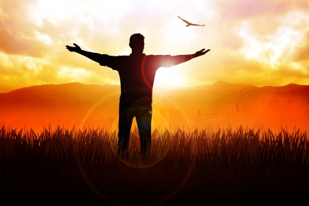 Silhouette illustration of a man standing on grass field with open arms facing the sun Stock Photo