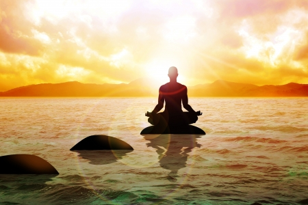 'peace of mind': Silhouette of a man figure meditating on calm water during sunrise  Stock Photo