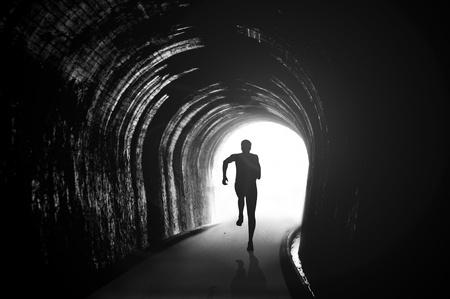 huir: Silueta de ilustraci�n de una figura que corr�a en el t�nel Foto de archivo