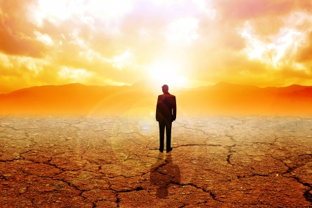 hopelessness: A man figure standing on dry land Stock Photo