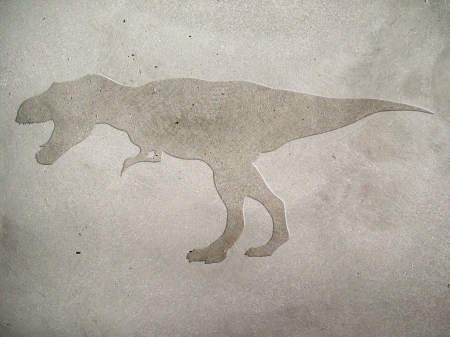 Image of tyrannosaur embossed on concrete wall
