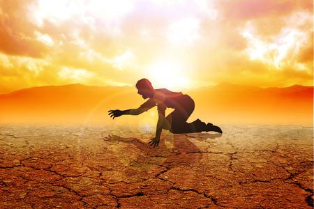 sediento: Silueta de un hombre que se arrastra en la tierra árida Foto de archivo