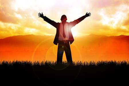 A man standing on grass field with open arms with mountain and sunrise as the background Stock Photo